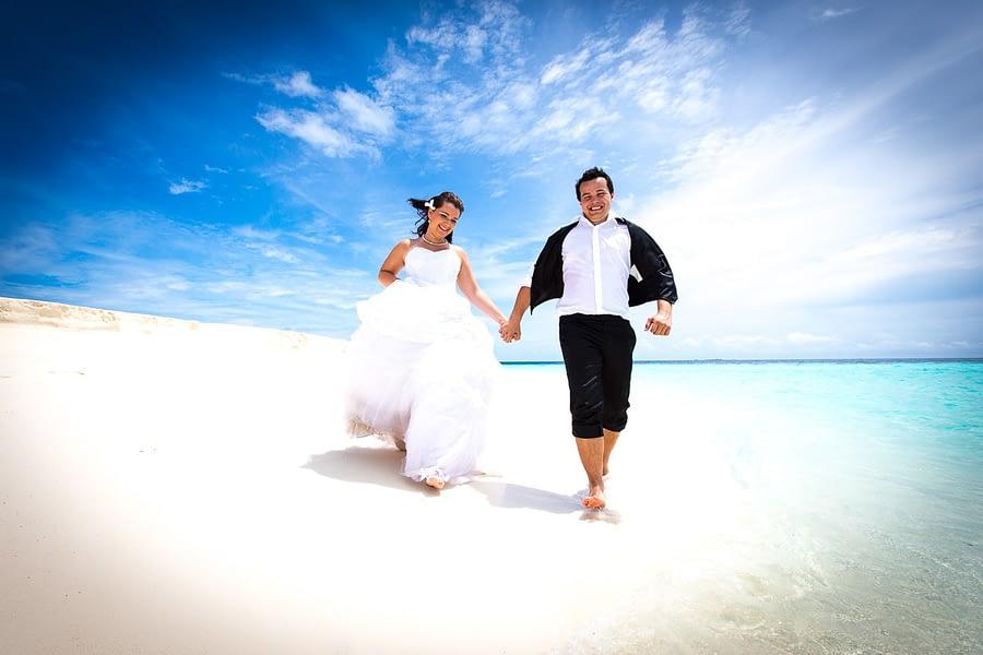 Brautpaar rennt auf Fotograf zu am Strand
