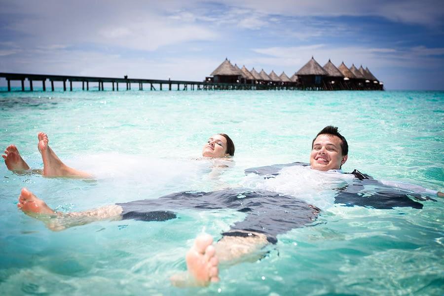 Paar mit Kleid und Anzug im Wasser